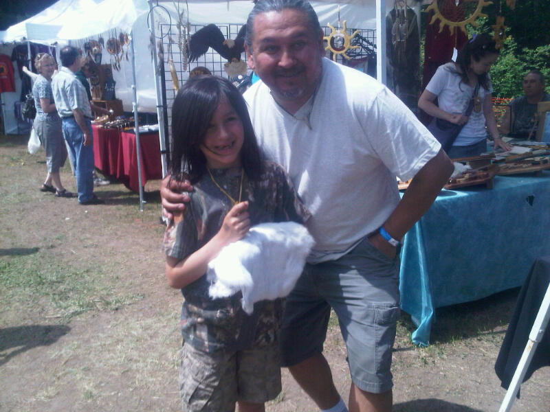 A young Odawa Festival attendee meets a new friend from one of the craft stalls.
