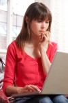 Worried Young Woman Using Laptop At Home