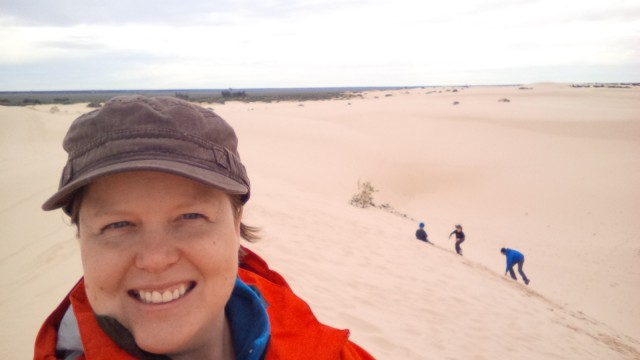 Sand dune selfie! :) Family can be seen sand surfing in the background.